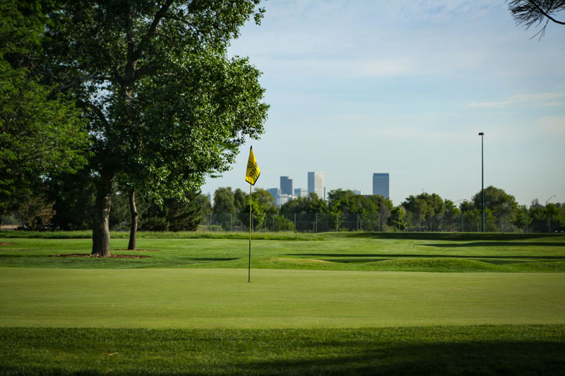 View of the flag on Hole #8 green with city skyline in background at Overland Park