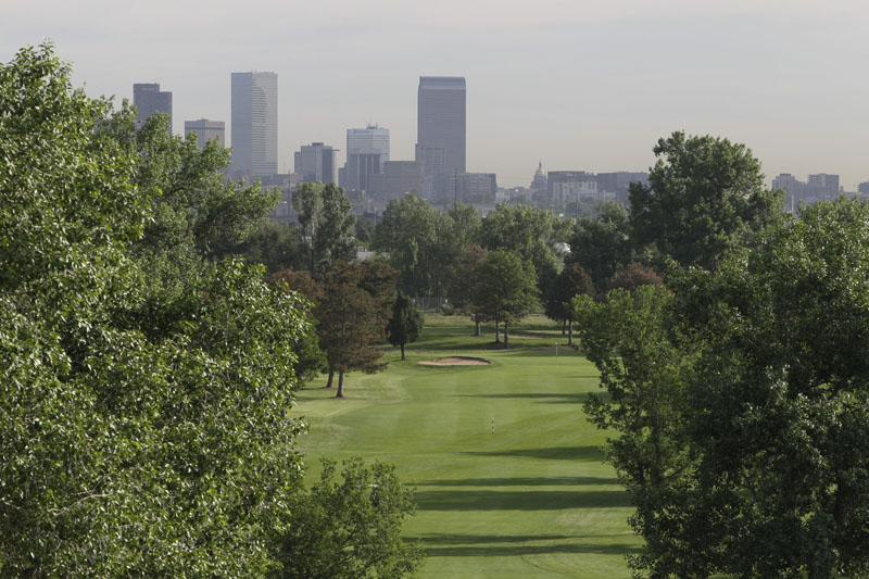 An above look at hole #15 with skyline in background at Overland Park